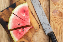 Watermelon and old knife on the table Stock Photography