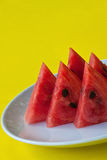 Watermelon pieces. On white plate, yellow blackground Royalty Free Stock Photo