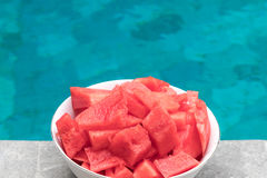 Watermelon pieces in bowl near the swimming pool. stock photography