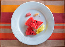 Watermelon and Pineapple with Chili Sugar and Plum Salt. Served on round white plate and colourful cloth coaster Stock Photo