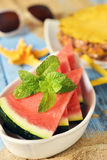Watermelon, pineapple, starfish and sunglasses. Closeup of a bowl with some slices of watermelon on a blue rustic wooden surface next to some yellow starfishes Stock Photography