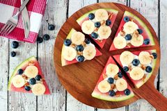 Watermelon pizza with bananas, blueberries and yogurt on serving board Royalty Free Stock Images