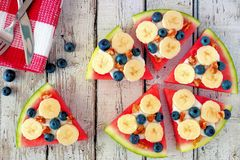 Watermelon pizza with bananas, blueberries and yogurt on white wood Stock Image