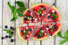 Watermelon pizza with blueberries, feta and mint, scene on white wood Stock Photo