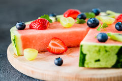 Watermelon pizza cut with fruits on wooden board, close up royalty free stock photography
