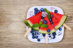 Watermelon popsicle and blueberries on old wood background Stock Image