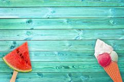 Watermelon popsicle and ice cream cone on blue planks background with copy space. Summer concept Royalty Free Stock Images