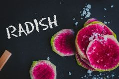 Watermelon Radishes Sliced, Sprinkled with Sea Salt. On a black background Royalty Free Stock Image