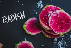 Watermelon Radishes Sliced, Sprinkled with Sea Salt. On a black background Royalty Free Stock Photography