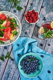 Watermelon, raspberries and blueberries in a bowl. Watermelon and berries in a bowl on a blue tablecloth and old wood. Summer composition. Blue tone Royalty Free Stock Photography