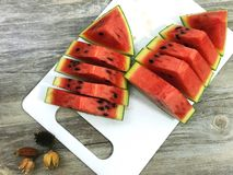 pieces of refreshing watermelon. Closeup of some pieces of refreshing watermelon on a white chopping block Royalty Free Stock Photo