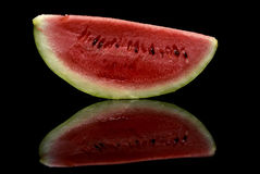 Watermelon Reflection. A slice of watermelon on a reflective background Royalty Free Stock Images