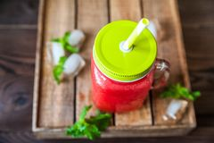 Watermelon refreshing smoothie in a jar close-up and copy space. Watermelon smoothie with a heart of watermelon, mint, ice on a te. Xtured red brick wall royalty free stock image