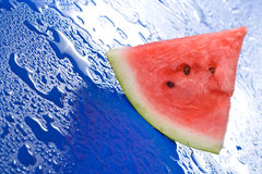 Watermelon slice on blue surface Stock Photo