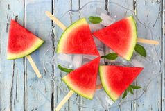 Watermelon slice pops on clear plate against rustic blue wood. Watermelon slice popsicles on clear plate with a rustic blue wood background Stock Image