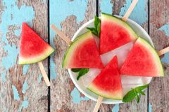 Watermelon slice pops on plate against rustic blue wood. Watermelon slice popsicles on plate with a rustic blue wood background Stock Image