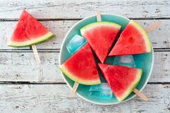 Watermelon slice popsicles on blue plate over rustic wood Stock Images