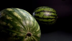 Watermelon slice rotation on a black background. Slow motion. Two Green huge fresh wet tasty striped Watermelons slider skating and rotation on a black stock video footage