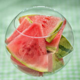 Watermelon. Slices in big  round  glass on checkered background Royalty Free Stock Images