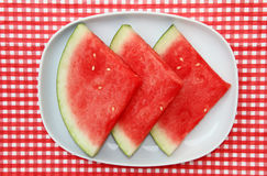 Watermelon Slices on dish, platter. Watermelon Slices on dish on red and white checkered background Royalty Free Stock Photography