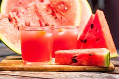 Watermelon slices and juice on wooden table. Glasses with watermelon juice and ice and sliced fresh ripe watermelon. Delicious summer diert concept. Selective Royalty Free Stock Photography
