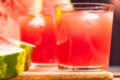 Watermelon slices and juice on wooden table. Glasses with watermelon juice and ice and sliced fresh ripe watermelon. Delicious summer diert concept. Selective Royalty Free Stock Image