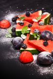Sliced watermelon with blackberries and mint leaves on black backgroung. Healthy vegetarian food. Watermelon slices and mint leaves on white backgroung. А royalty free stock photo