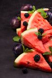 Sliced watermelon with blackberries and mint leaves on black backgroung. Healthy vegetarian food. Watermelon slices and mint leaves on white backgroung. А stock image