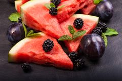 Sliced watermelon with blackberries and mint leaves on black backgroung. Healthy vegetarian food. Watermelon slices and mint leaves on white backgroung. А stock photo