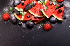 Sliced watermelon with blackberries and mint leaves on black backgroung. Healthy vegetarian food. Watermelon slices and mint leaves on white backgroung. А royalty free stock images