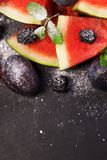 Sliced watermelon with blackberries and mint leaves on black backgroung. Healthy vegetarian food. Watermelon slices and mint leaves on white backgroung. А royalty free stock photos