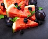 Sliced watermelon with blackberries and mint leaves on black backgroung. Healthy vegetarian food. Watermelon slices and mint leaves on white backgroung. А royalty free stock image