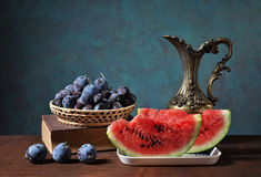 Watermelon slices and plums in wickerbasket Royalty Free Stock Image