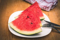Watermelon slices on the white porcelain plate, served with cutlery and napkin, Royalty Free Stock Images