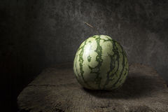 Watermelon with smile on old wooden table. Royalty Free Stock Images