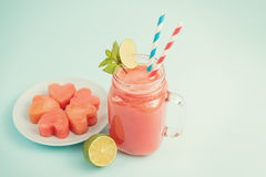 Watermelon smoothie in Mason jar decorated with lime, mint, straws Stock Image