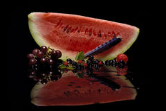 Watermelon Still Life. A slice of watermelon with mixed fruit on a reflective background Royalty Free Stock Image