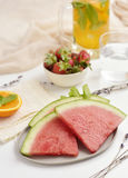 Watermelon, strawberries and cold tea. Some slices of watermelon in a ceramic plate, a white ceramic bowl with strawberries and a jar with cold tea on a white a Stock Photography