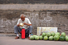 A watermelon street seller eats his lunch, pingyao, china Royalty Free Stock Photography