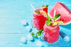 Watermelon summer cocktail with ice and mint leaves. Cold refreshment drink on blue wooden background with copy space. royalty free stock image