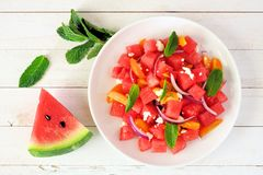 Watermelon and tomato salad, top view table scene over white wood. Watermelon and tomato salad with feta cheese. Top view on white plate. Table scene with a stock photo