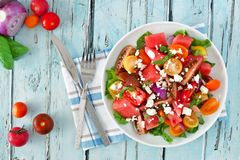 Watermelon and tomato salad with feta, overhead on blue wood. Watermelon and mixed tomato salad with feta cheese, overhead scene on rustic blue wood Royalty Free Stock Image