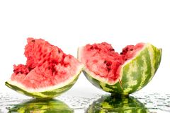Watermelon halves pieces with cracks and water drops on white mirror background with reflection isolated close up royalty free stock photography