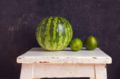 Watermelon and two green lemons Royalty Free Stock Photos