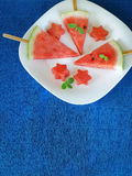 Watermelon. Watermelon pieces formed as popsicles and as stars on a white plate. On a blue colourful background stock images