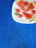 Watermelon. Watermelon pieces formed as popsicles and as stars on a white plate on a blue colourful background Stock Images