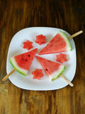 Watermelon. Watermelon pieces formed as popsicles and as stars on a white plate. On a wooden background. Unusual watermelon serving stock photography