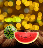 Watermelon on wooden tabel with yellow bokeh light. Background Royalty Free Stock Images