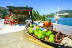 Watermelons at food stand. Watermelons in a boat and fresh homemade fruit juices on a barrel displayed at a food stand next to the river Neretva in Croatia stock image