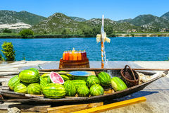 Watermelons at food stand. Watermelons in a boat and fresh homemade fruit juices on a barrel displayed at a food stand next to the river Neretva in Croatia stock images